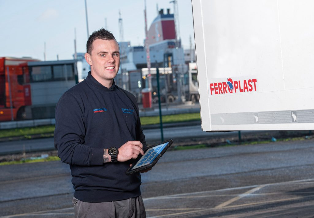 Technician at Belfast Port Commercials using Freeway Fleet Systems on a tablet whilst doing a completing a digital job card as part of a trailer service